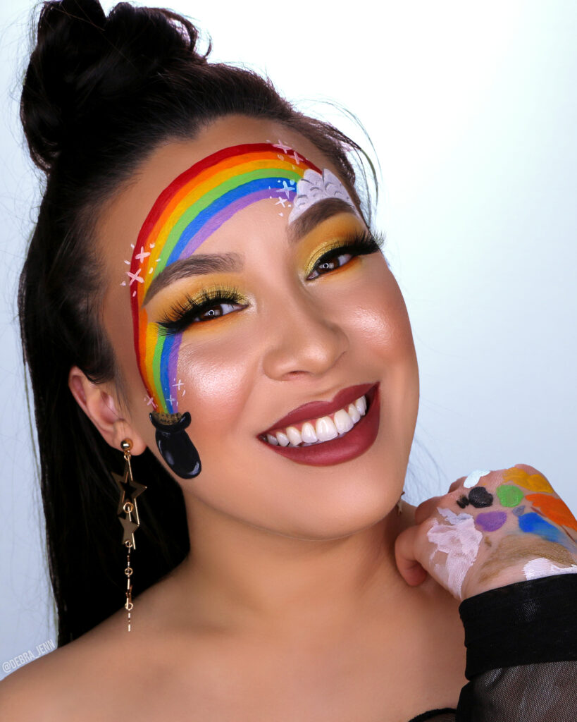 St Patricks Day Makeup with gold eyeshadow and pot of gold with rainbow painted on face