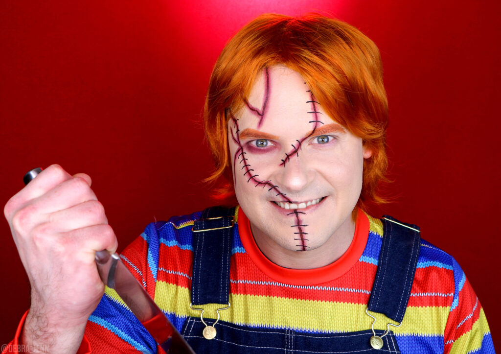 chucky doll makeup with scars painted on face, bright orange hair, overalls and bright shirt, holding a knife menacingly