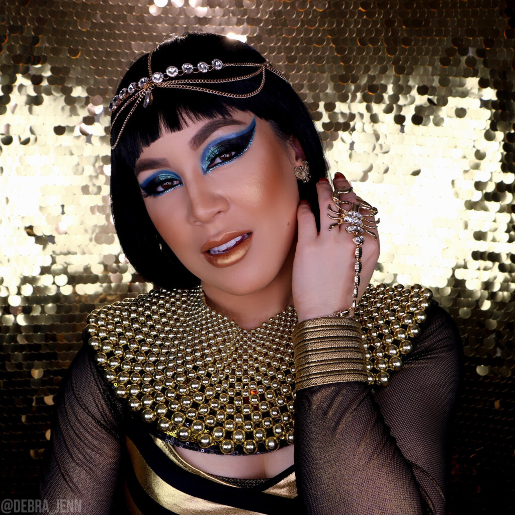 Cleopatra makeup and halloween costume with dramatic blue eyeshadow and lots of gold jewelry
