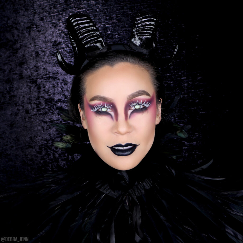 dark angel makeup for halloween with black ram horns and feathers, white lashes, and glowing eyes