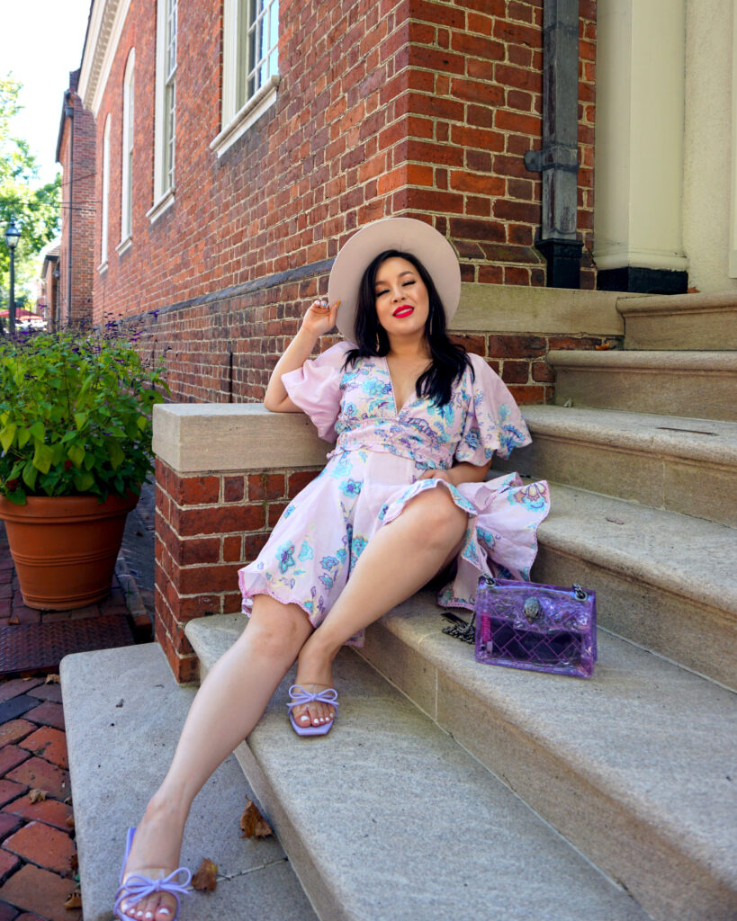 Debra Jenn wearing purple summer dress, clear purple purse, and hat, posed on stairs in colonial williamsburg